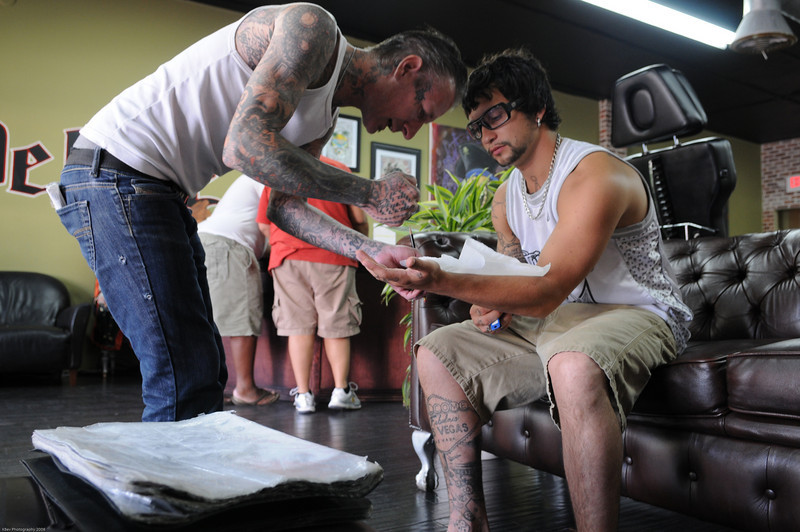 """Joe consulting an artist at the Love and Hate tattoo parlor (aka """"Miami Ink"""")"""