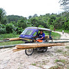 A traysikel (tricycle) transporting bamboo from one area to another