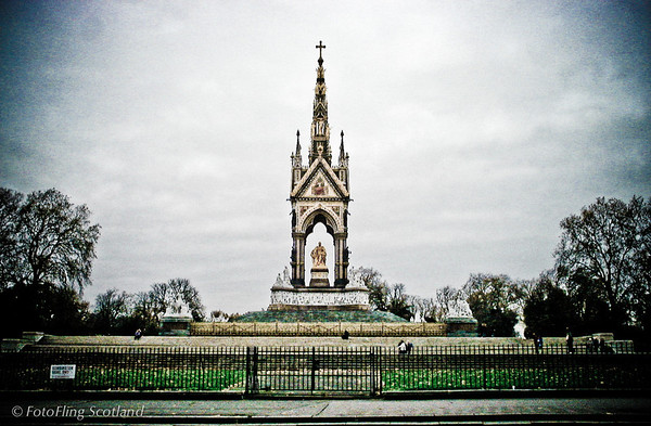 "Albert Memorial The Albert Memorial is situated in Kensington Gardens, London, England, directly to the north of the Royal Albert Hall. It was commissioned by Queen Victoria in memory of her beloved husband, Prince Albert who died of typhoid in 1861. The memorial was designed by Sir George Gilbert Scott in the Gothic revival style. Opened in 1872, with the statue of Albert ceremonially ""seated"" in 1875, the memorial consists of an ornate canopy or pavilion containing a statue of Prince Albert facing south. The memorial is 176 feet tall, took over ten years to complete, and cost £120,000."