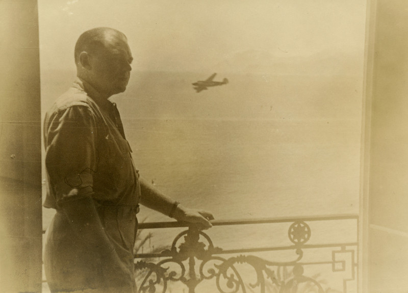Lt. Col Russell W. Hibbert Jr.<br /> Standing on the balcony of my room at the Carlton Hotel - Note the C47 in the distant background.