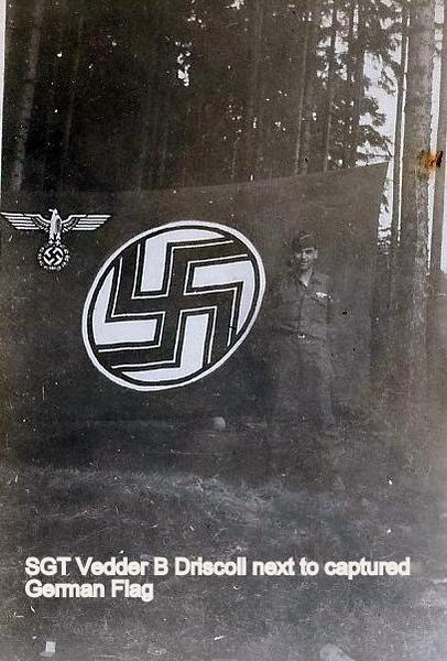 Vedder Driscoll next to captured German Flag -2