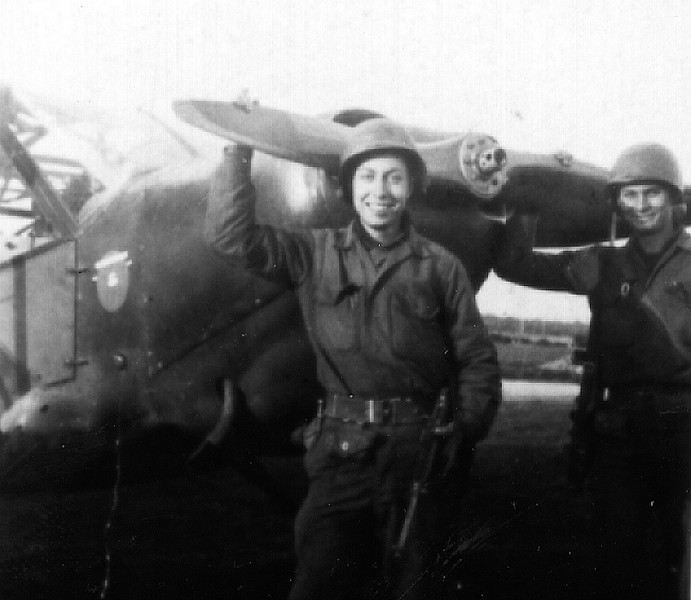 Jules Korn and Joe Wilson standing in front of an artillery observation plane, L-5 Piper.