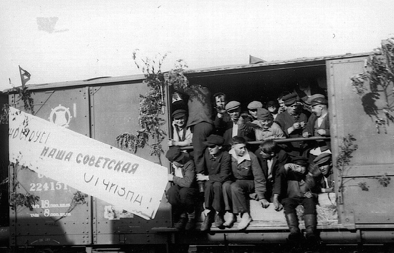 "Displaced persons being returned to their homelands.  Sign reads, ""Long Live Our Soviet Homeland.""  Photograph by William Parod."