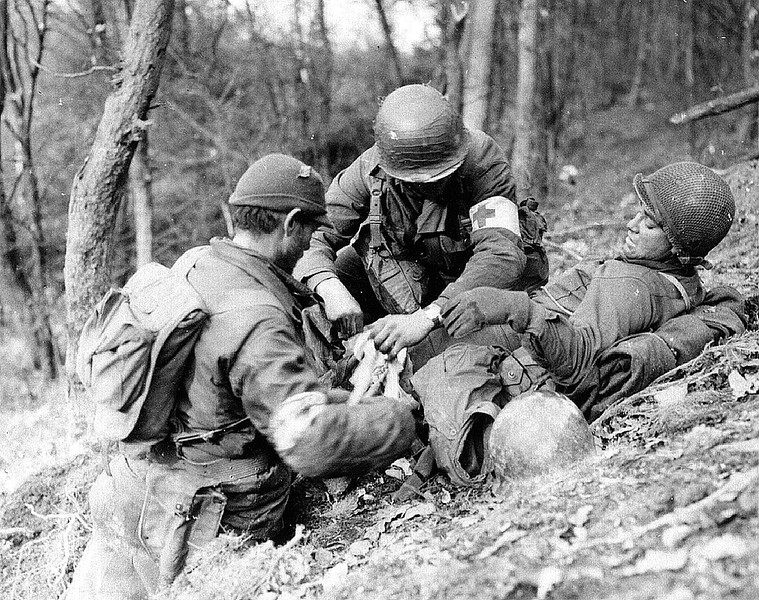 Two medics give medical aid to a wounded soldier.