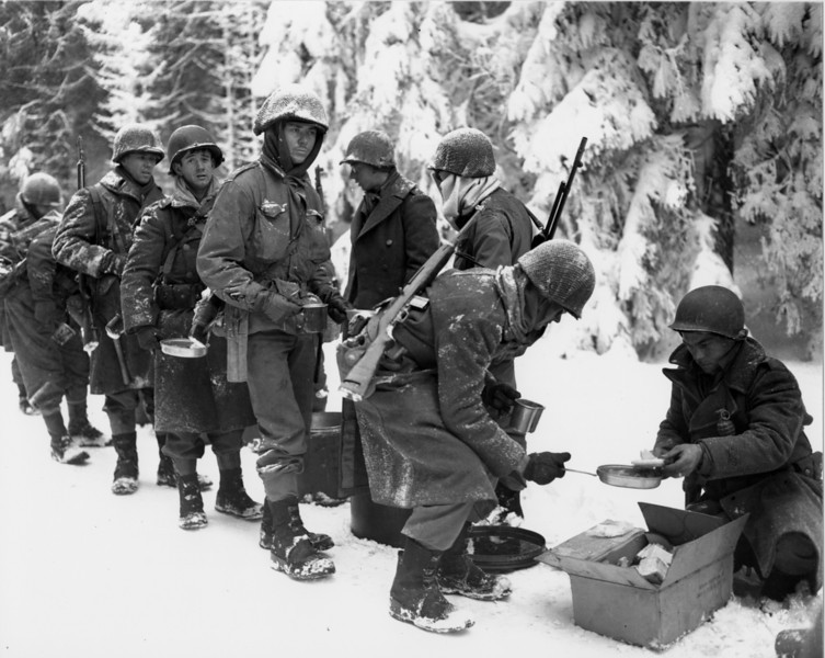 13 January 1945 - Near Saint-Hubert, Belgium<br /> Company I, 347th Infantry Regiment, 87th Infantry Division<br /> <br /> After vicious fighting in the sub-zero cold snows of the dense Ardennes Forest, soldiers receive a rare respite from the frontline intrantryman's usual foxhole fare of terror and frozen K-rations.<br /> <br /> The photo presented is U.S. Army Signal Corps photo SC-198849.  It has become one of the most widely publicized Battle of the Bulge scenes, and has been featured  in many books, magazines, and documentaries.