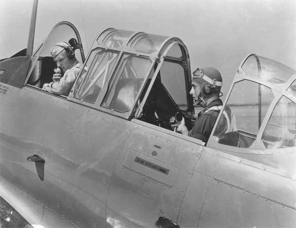 """A complete telephone system connecting A.C. instructor in the front cockpit and his Flying Cadet student pilot in the rear cockpit, a distance of 3 ft., is used at Randolph Field, Texas giant training field. Telephone dial is the only part that's missing…and of course, no """"busy signals""""."""