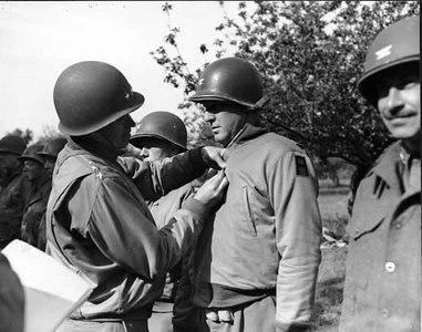 Lt. General Omar Bradley pins the Bronze Star on Colonel V.R. Pogue, one of the first group of officers and men to receive the award in World War II.
