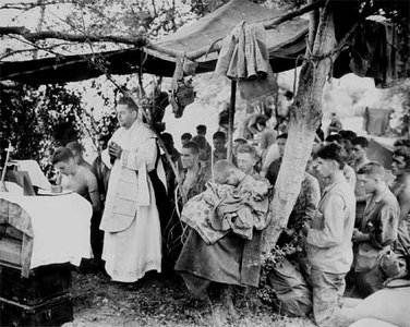 With a canvas tarpaulin for a church and packing cases for an altar, a Navy chaplain holds mass for Marines at Saipan. The service was held in memory of brave buddies who lost their lives in the initial landings.