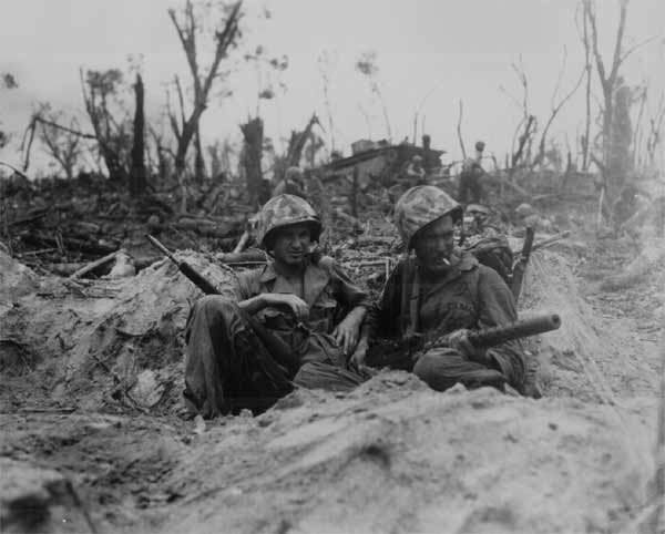 Marine Pfc. Douglas Lightheart (right) cradles his 30-cal. machine gun in his lap, while he and his buddy Pfc. Gerald Churchby take time out for a cigarette, while mopping up the enemy on Peleliu Is.