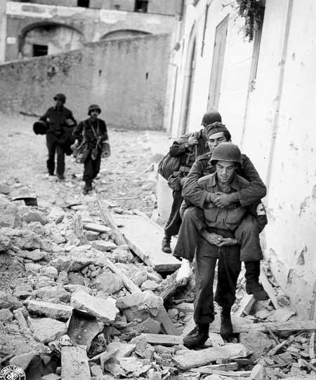 Medic carrying wounded German prisoner.