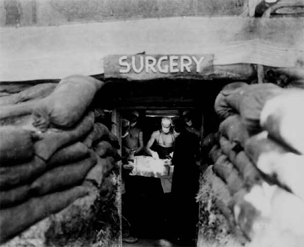 In an underground surgery room, behind the front lines on Bougainville, an American Army doctor operates on a U.S. soldier wounded by a Japanese sniper. December 13, 1943.
