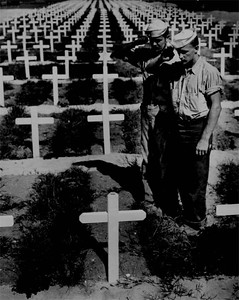 Standing in the grassy sod bordering row upon row of white crosses in an American cemetery, two dungaree-clad Coast Guardsmen pay silent homage to the memory of a fellow Coast Guardsman who lost his life in action in the Ryukyu Islands.