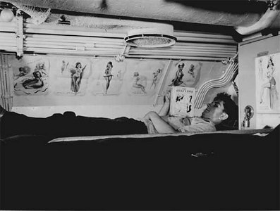 Sailor reading in his bunk aboard USS CAPELIN at submarine base New London, Conn.