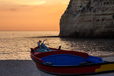 Boat along the coast at sunset