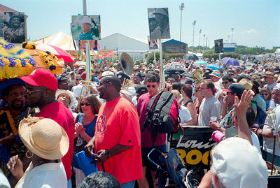 The festival crowd follows the jazz funeral