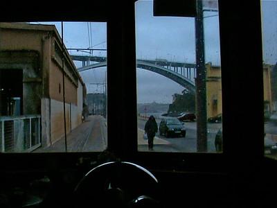 Ponte da Arràbida (Arràbida Bridge) rises behind the tram
