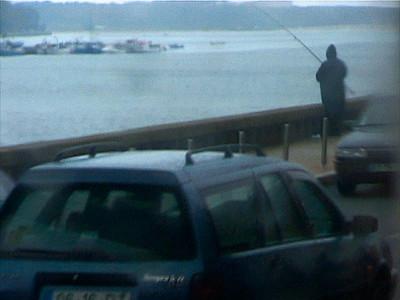 Hooded figure fishing