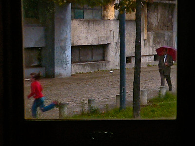 The running girl passes the old man in the rain