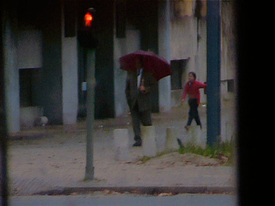 A young girl runs by a man near the tracks