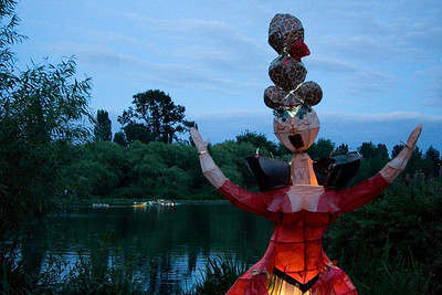 Lady with Gaudi-esque hair Glowing lanterns are rowed across the lake in the background
