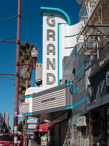 "2014: The freshened-up marquee of the Grand. The Gray Area arts organization (grayarea.org/theater) signed a ten-year lease to operate the Grand as an ""art and technology theater."" In the background, the New Mission marquee is wrapped during restoration."