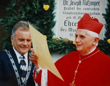 ** FILE ** German Cardinal Joseph Ratzinger, right, holds an unidentified document, as the mayor of the southern German town of Marktl, Hubert Gschwendtner looks on in Marktl, the hometown of Ratzinger, July 13, 1997. In background the honory citizen plaque at Ratingers birth place. Cardinal Joseph Ratzinger of Germany, a longtime guardian of doctrinal orthodoxy, was elected the new pope Tuesday, April 19, 2005 evening in the first conclave of the new millennium. He chose the name Pope Benedict XVI. (AP Photo/Gemeinde Marktl)