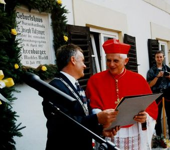 ** FILE ** German Cardinal Joseph Ratzinger, right, holds a document, with the mayor of the southern German town of Marktl, Hubert Gschwendtner in Marktl, the hometown of Ratzinger, in this July 13, 1997 file photo. In background an honory citizen plaque identifies the building as Ratzingers birth place. Cardinal Joseph Ratzinger of Germany, a longtime guardian of doctrinal orthodoxy, was elected the new pope Tuesday, April 19, 2005 evening in the first conclave of the new millennium. He chose the name Pope Benedict XVI. (AP Photo/Gemeinde Marktl)