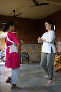 A student teaches an Indian dance step to Linda.