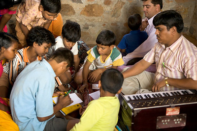 Children gather in the performance space. The music teacher will play the harmonium for the dance performance.