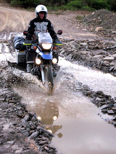 Allan rides into a muddy cesspool created by trucks making the run from Sucre to Santa Cruz.