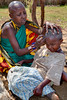 A young Masai girl getting an unwanted haircut