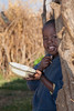 A yound Masai boy eating breakfast