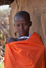 A young Masai boy leaning against a cow dung and mud home.