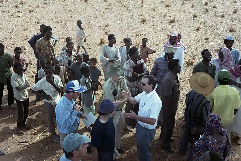 French, English, American & Nigerien leaders confer at a proposed test site. Many young men from a nearby village congregate to observe what may be the most exciting show in the area.