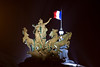 The French flag and statue atop a building near the Seine.