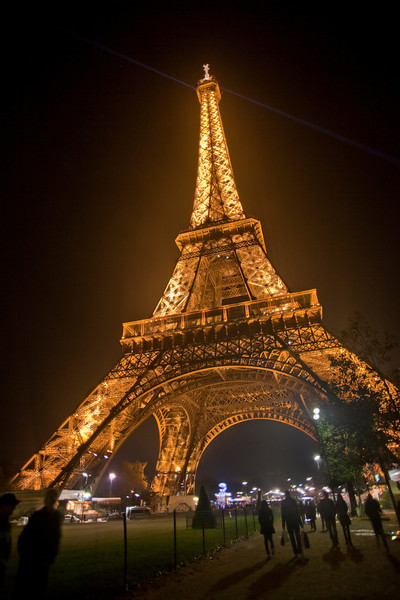 A veiw of the Eiffel Tower at night along the promenade.