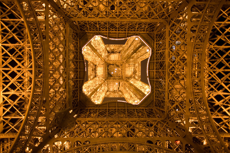 Looking straight up from directly under the Eiffel Tower at night.