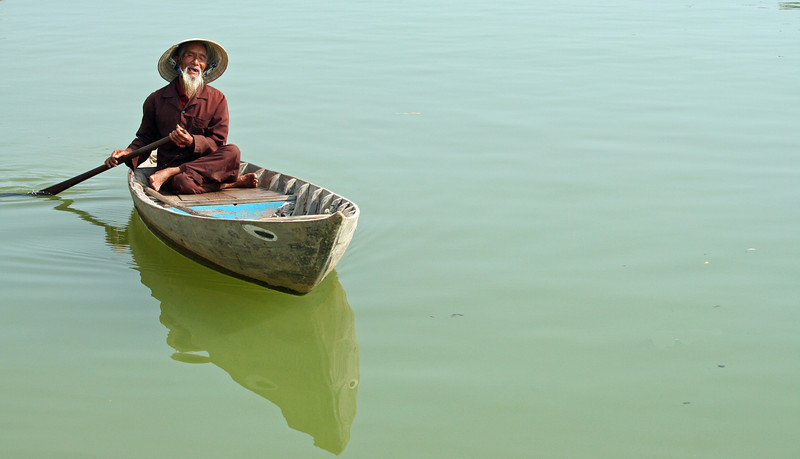 Elderly man paddling on the Mekong River