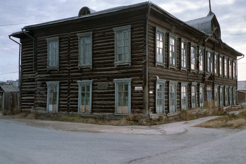 Yakutsk is built entirely on permafrost. Over the decades the heat from the buildings causes some melting, the soil collapses, and the buildings buildings sink into the ground. Note the window ledges just barely above the ground.