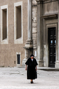 A lonely nun walks around Basilica of St.Paul Outside the Walls, Rome, Italy