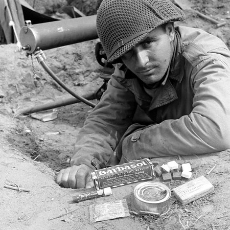 """An American soldier showing off some personal items in Anzio, here is the original caption from the photographer. William P. Chirolas. """"things that men in M Company don't like: Dextrose tablets — taste terrible, almost invariably thrown away; Barbasol — they don't like brushless shaving cream, say it sticks in the razor; Fleetwood cigarettes — typical of the cheap cigarettes that come in the K rations; processed American cheese — gets very tiresome when eaten day after day. . . ."""" #WWII #ww2history #WW2"""