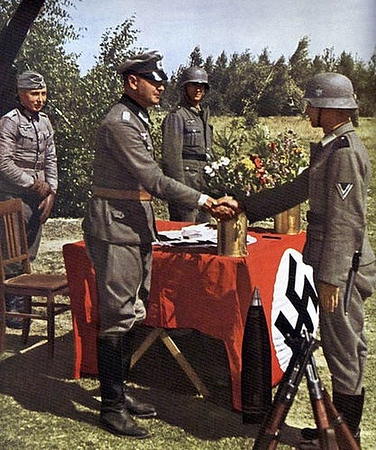 A German soldier being promoted by his company-CO. Maybe a Panzer division? (the piping on the COs crusher looks pink, but I'm not sure) Even though in the field, the act of promotion is being celebrated. Notice how the Kar98s are put together to form a pyramid. #WWII #ww2history #WW2 #german