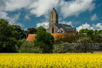 Old church and rapeseed field in Normandy, France