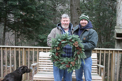 Paul and Erik concentrated on crafting a spruce wreath adorned with burgundy red rose hips and pinecones from a yellow pine tree.