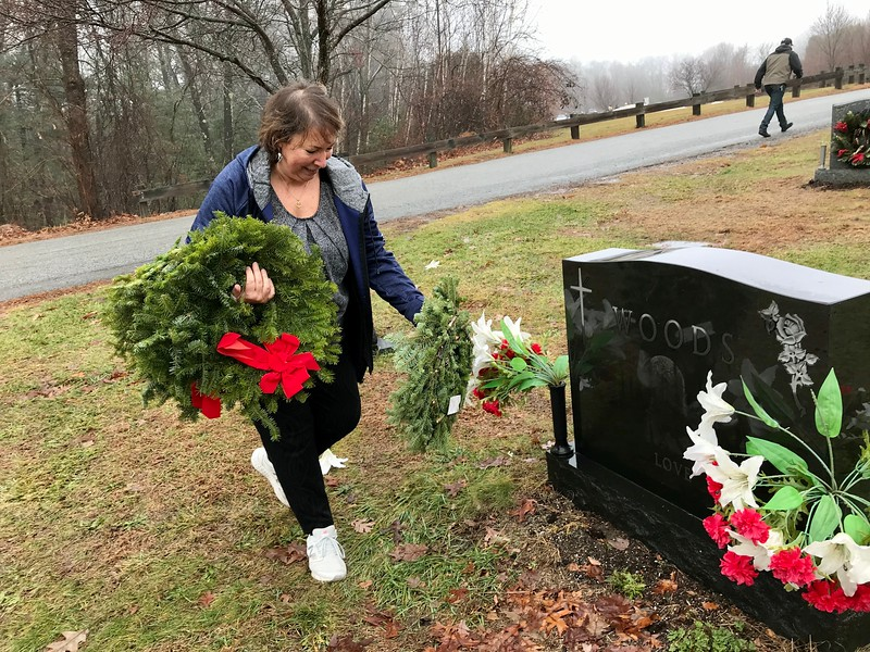 Carol Woods prepared to place a wreath on her father-in-laws grave at Fox Hill Cemetery. Photo by Mary Leach