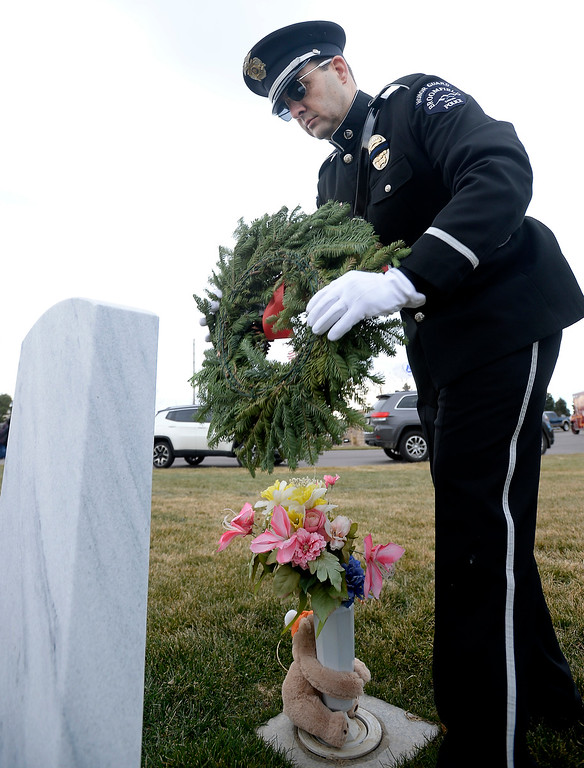 . BROOMFIELD, CO - December 15, 2018: Drew Wilson, of the Broomfield Police Department, places a wreath at a veteran\'s grave at the Broomfield County Commons Cemetery on December 15, 2018. The Broomfield Rotary Club held a wreath-laying ceremony at Broomfield\'s two cemeteries. Wreaths are meant to honor veterans in all branches throughout the holidays.  (Photo by Cliff Grassmick/Staff Photographer)