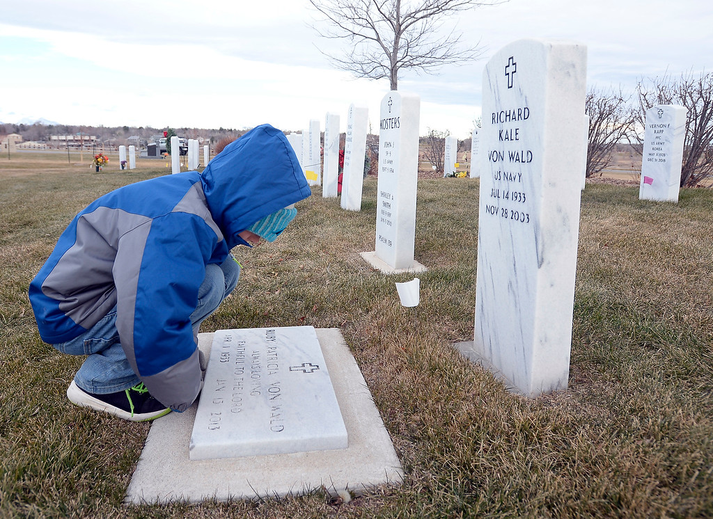 . BROOMFIELD, CO - December 15, 2018: Jackson Head, 9, looks closer at  a headstone at the BroomfieldCounty Commons Cemetery on December 15, 2018. The Broomfield Rotary Club held a wreath-laying ceremony at Broomfield\'s two cemeteries. Wreaths are meant to honor veterans in all branches throughout the holidays.  (Photo by Cliff Grassmick/Staff Photographer)