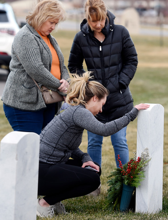 . BROOMFIELD, CO - December 15, 2018: Annie Klauck, bottom, puts a wreath at her father\'s gravesite with her mother, Patty Klauck, left, and her aunt, Marty Paluch, at the Broomfield County Commons Cemetery on December 15, 2018. The Broomfield Rotary Club held a wreath-laying ceremony at Broomfield\'s two cemeteries. Wreaths are meant to honor veterans in all branches throughout the holidays.  (Photo by Cliff Grassmick/Staff Photographer)