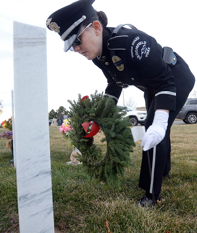 . BROOMFIELD, CO - December 15, 2018: Caitlyn Hollifield, of Broomfield Police, puts a wreath on a veteran\'s grave at the Broomfield County Commons Cemetery on December 15, 2018. The Broomfield Rotary Club held a wreath-laying ceremony at Broomfield\'s two cemeteries. Wreaths are meant to honor veterans in all branches throughout the holidays.  (Photo by Cliff Grassmick/Staff Photographer)