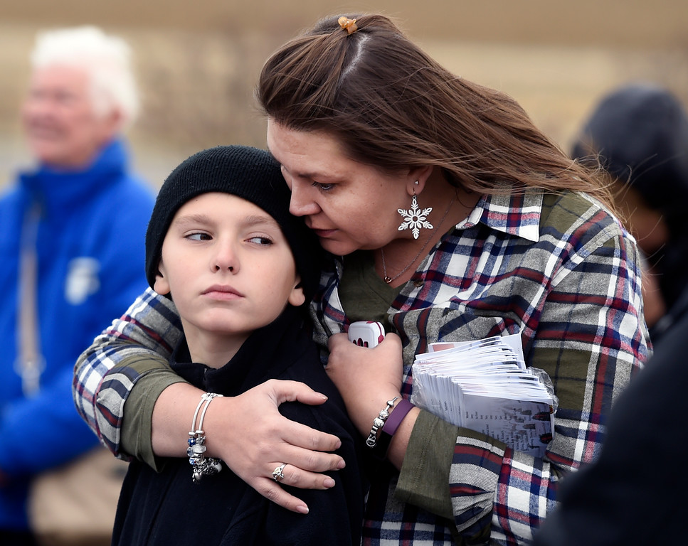 . BROOMFIELD, CO - December 15, 2018: Samantha Duggan has a quiet moment with her son, Connor, 10, during the ceremony at the Broomfield County Commons Cemetery on December 15, 2018. The Broomfield Rotary Club held a wreath-laying ceremony at Broomfield\'s two cemeteries. Wreaths are meant to honor veterans in all branches throughout the holidays. For more photos, go to dailycamera.com.  (Photo by Cliff Grassmick/Staff Photographer)